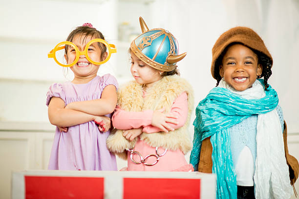 Little Girls in Costume Little girls dressed in theatrical costume laughing and smiling together. dressing up stock pictures, royalty-free photos & images