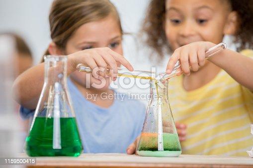 istock Little girls in elementary STEM class pour liquids into beaker 1159500415