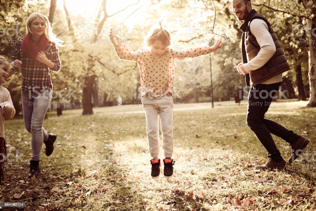 Little girls in park with parents playing with jump rope. royalty-free stock photo