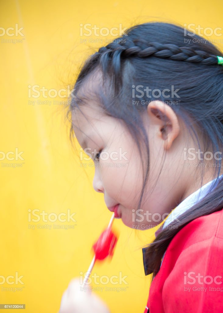 Little girls in red student dressed Eating a red popsicle royalty-free stock photo