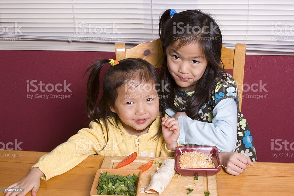 Little girls infront of tortilla wrap and ingredients royalty-free stock photo