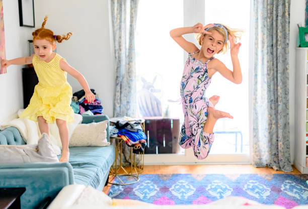Little girls jump and play in a messy living room stock photo