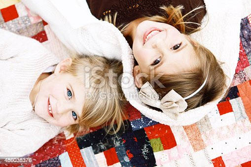 Two beautiful little sisters smile at the camera as they lay on a vintage quilt. Image can be used vertically or horizontally.