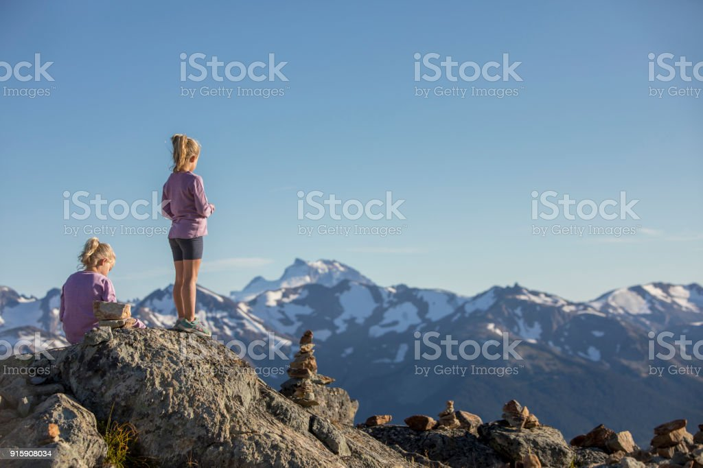 Little girls looking at view at top of mountain. stock photo