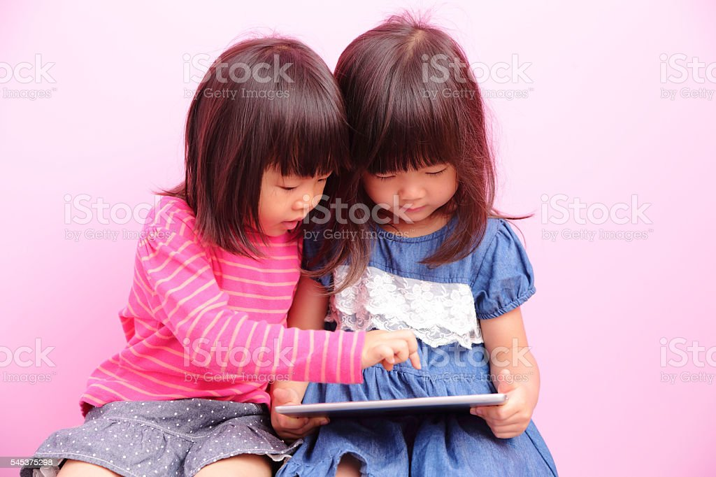 little girls looking front together stock photo
