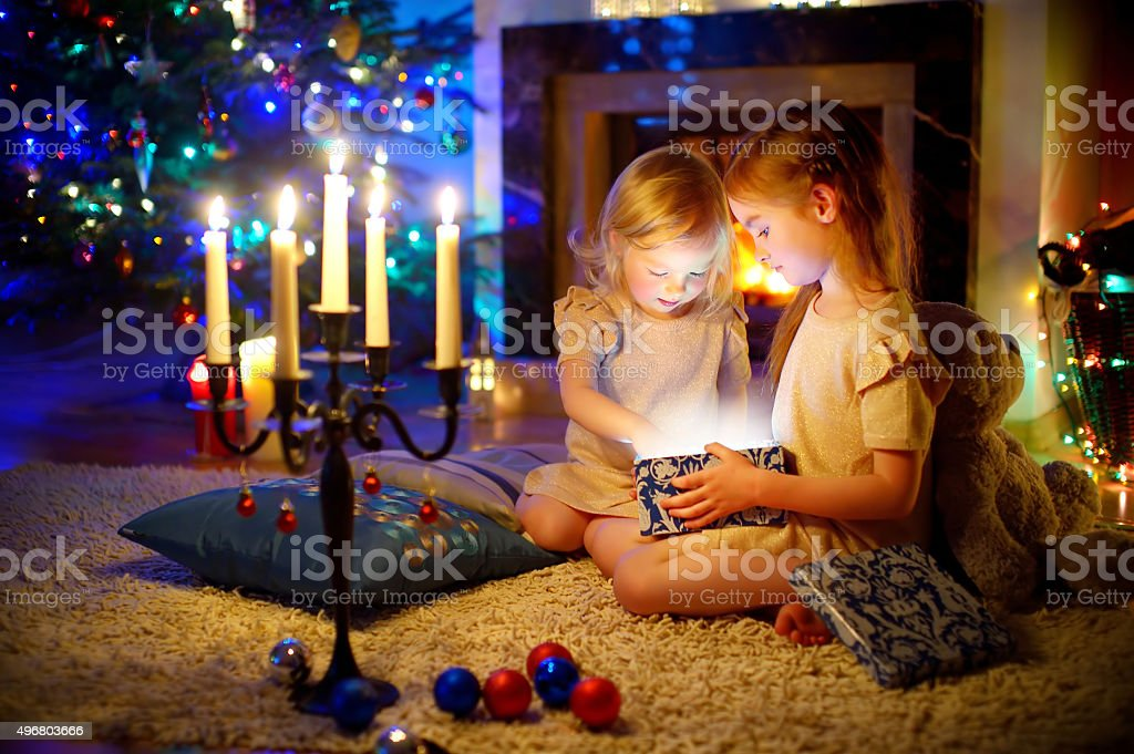 Little girls opening a magical Christmas gift stock photo