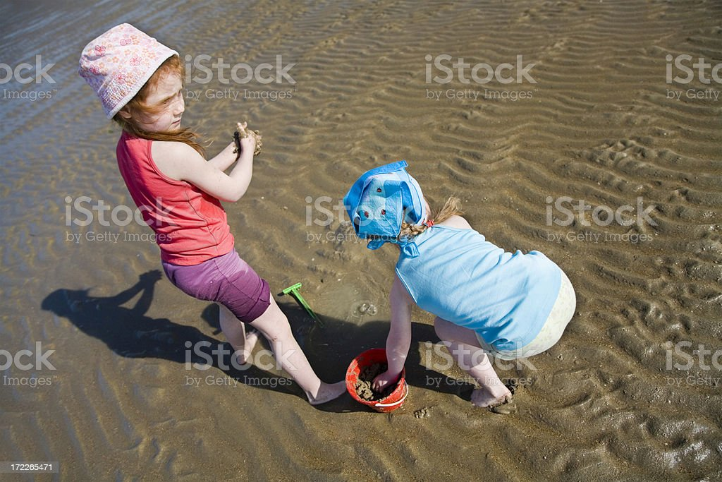 "Little girls playing barefoot at the sea ""Little 4 and 6 year old girls at the beach, on a hot sunny day, playing in the sea sand and water.Location: Gravelines, France."" 4-5 Years Stock Photo"