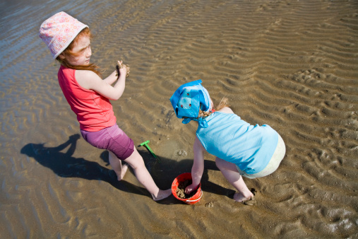 Little Girls Playing Barefoot At The Sea Stock Photo - Download Image Now