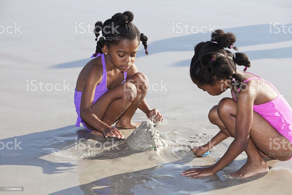 Little girls playing in sand at beach royalty-free stock photo