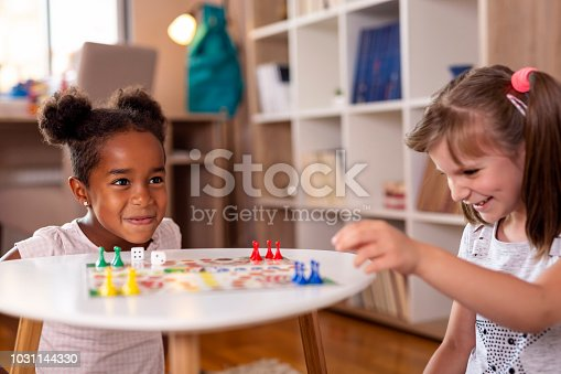 Two little girls sitting in a playroom, playing a ludo board game; one of them just won the game. Focus on the girl on the left