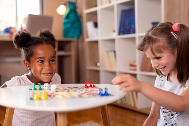 little girls playing ludo board game - leisure games stock pictures, royalty-free photos & images