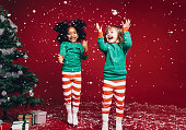 Little girls in christmas costume having fun and jumping beside a decorated christmas tree. Two kids playing with falling artificial snow flakes near a christmas tree.