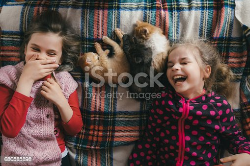 Little  Caucasian girls playing with kitten on the bed