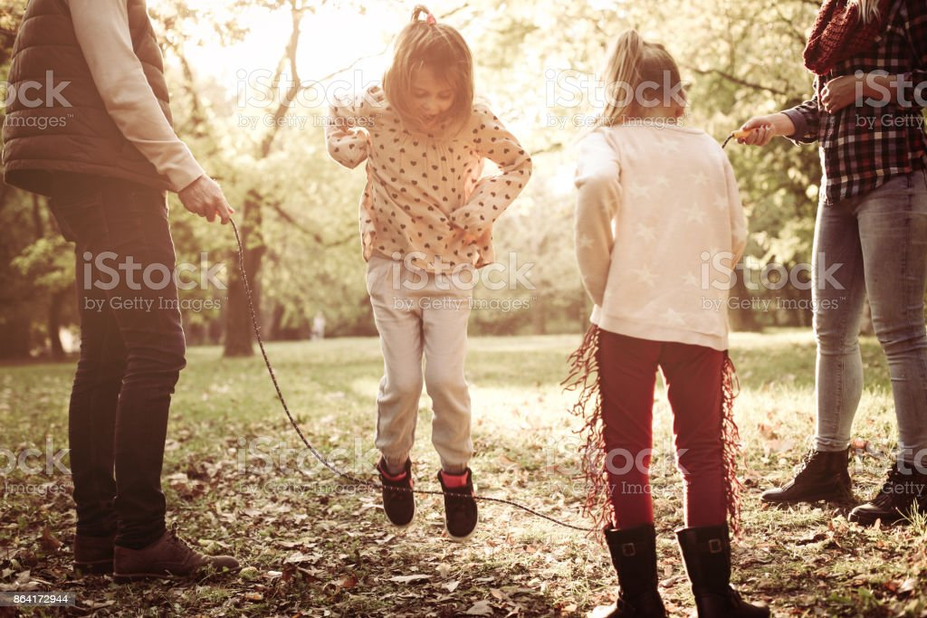Little girls playing with parents in park and jumping across jump rope . royalty-free stock photo