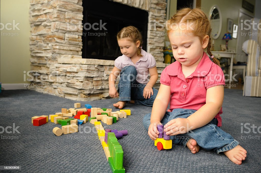 Little Girls Playing with Wooden Blocks on Carpet at Home royalty-free stock photo