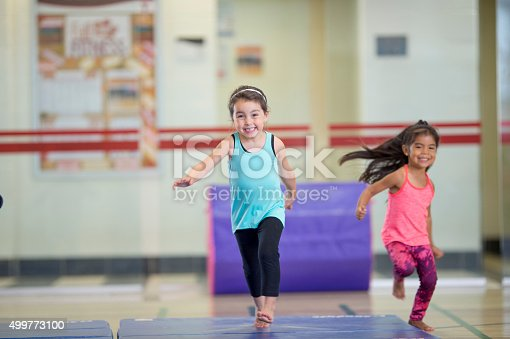 A multi-ethnic group of elementary age girls are running to warm up before gymnastics class. They are both smiling and looking at the camera.