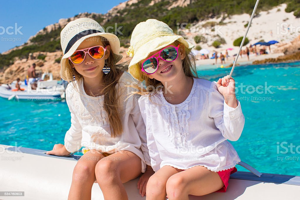 Little girls sailing on boat in clear open sea stock photo