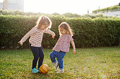 istock Little girls sisters playing with ball in summer park. Kids siblings having fun outdoors. 1226887390