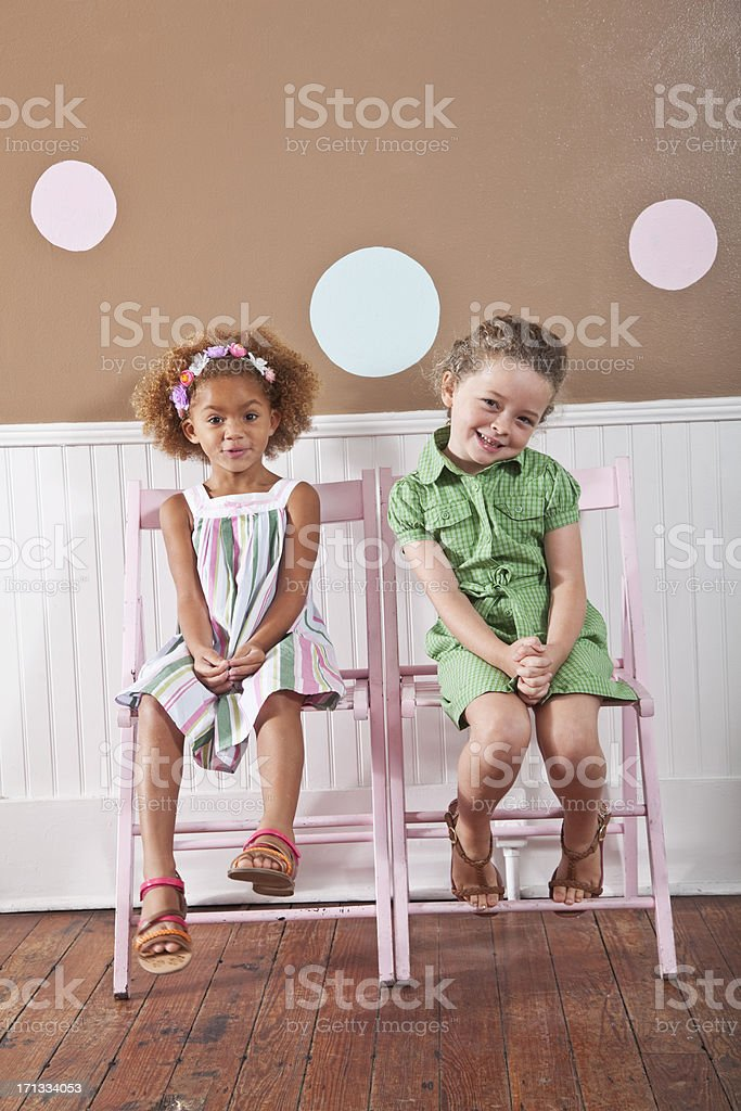 Little girls sitting on chairs stock photo