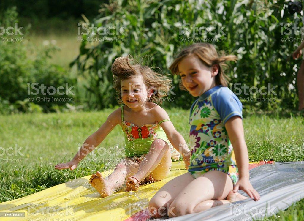 Little Girls Sliding on Water Slide in Summer stock photo