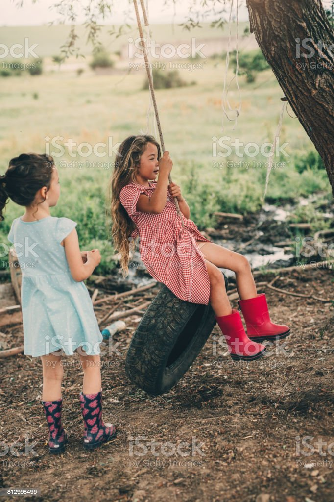 Little girls swinging on a tire stock photo