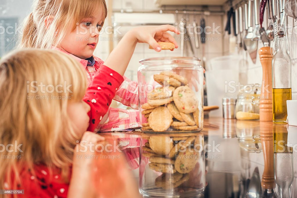 Little Girls Taking Oatmeal Cookies from a Jar stock photo