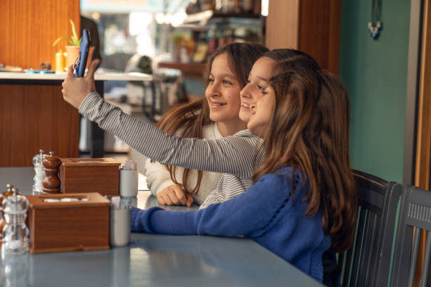 little girls taking selfie at the restaurant stock photo