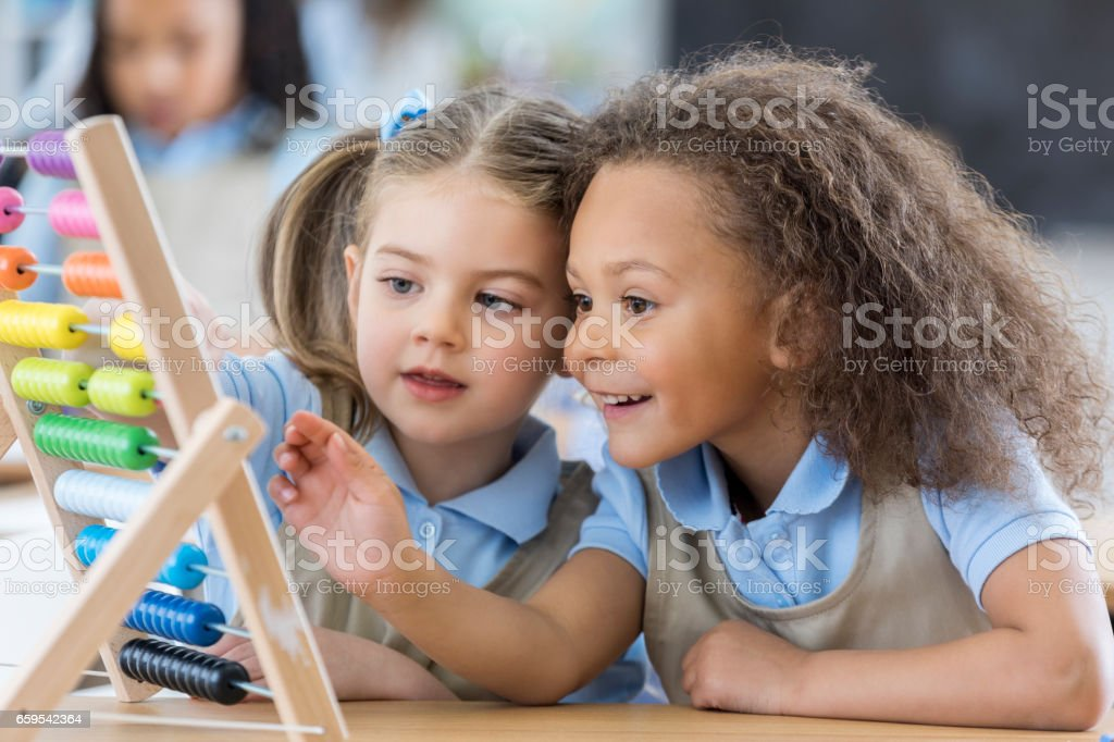 Little girls use abacus during preschool stock photo