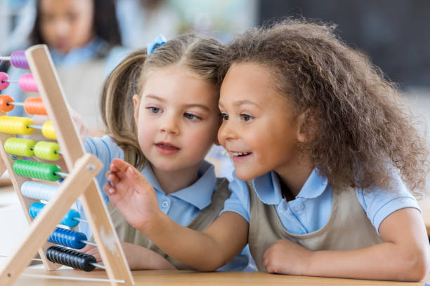 Little girls use abacus during preschool - foto stock