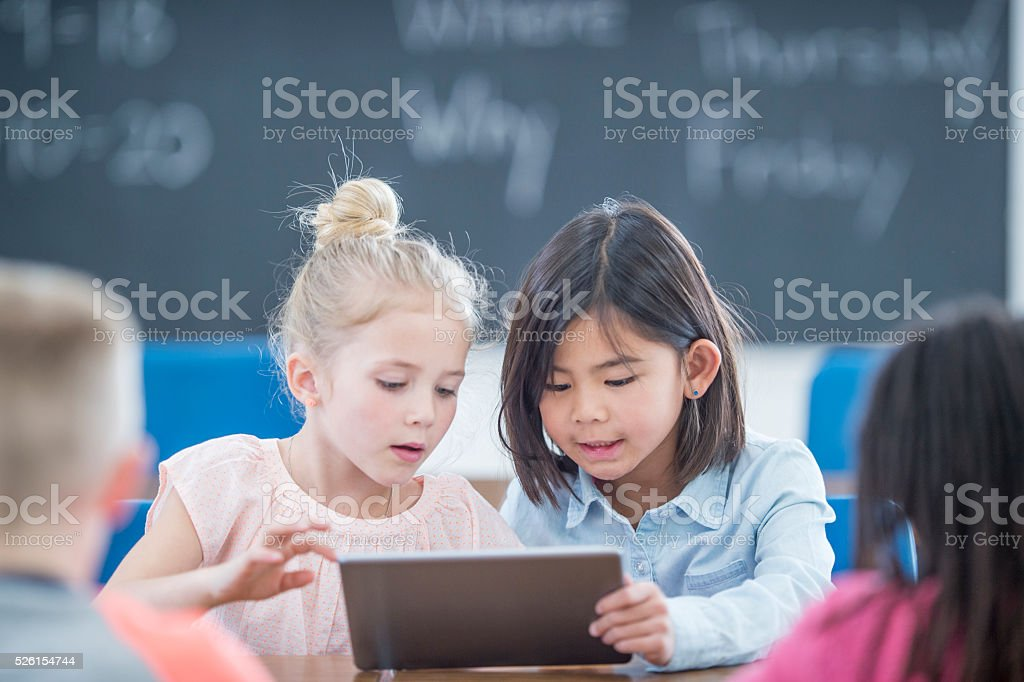 Little Girls Using a Digital Tablet stock photo