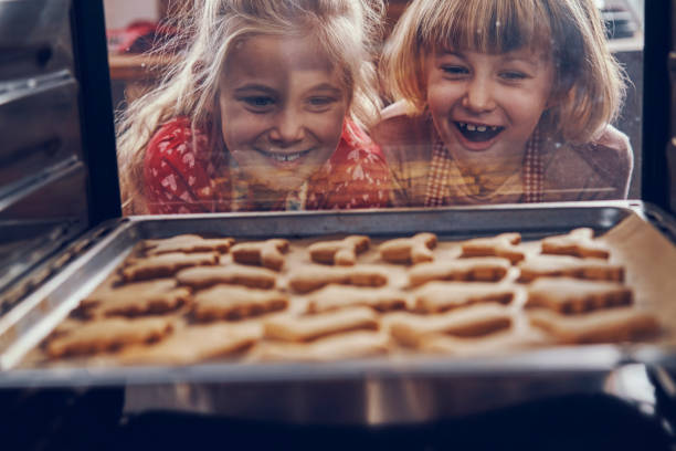 little girls waiting for christmas cookies to bake in the oven - christmas cookies stock pictures, royalty-free photos & images