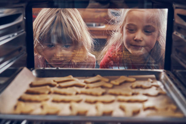 little girls waiting for christmas cookies to bake in the oven - christmas cooking imagens e fotografias de stock