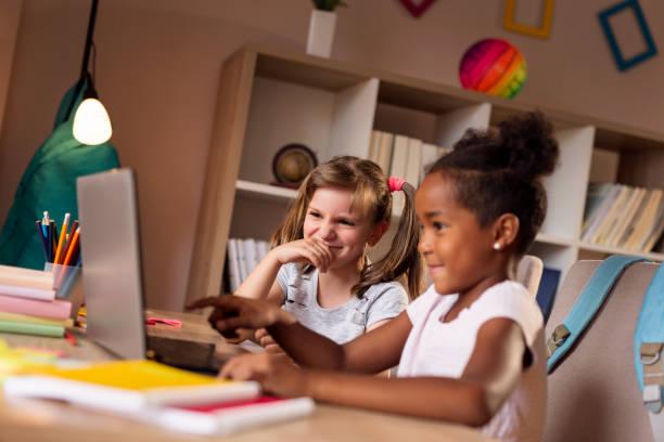 Little girls watching cartoons on a laptop computer stock photo