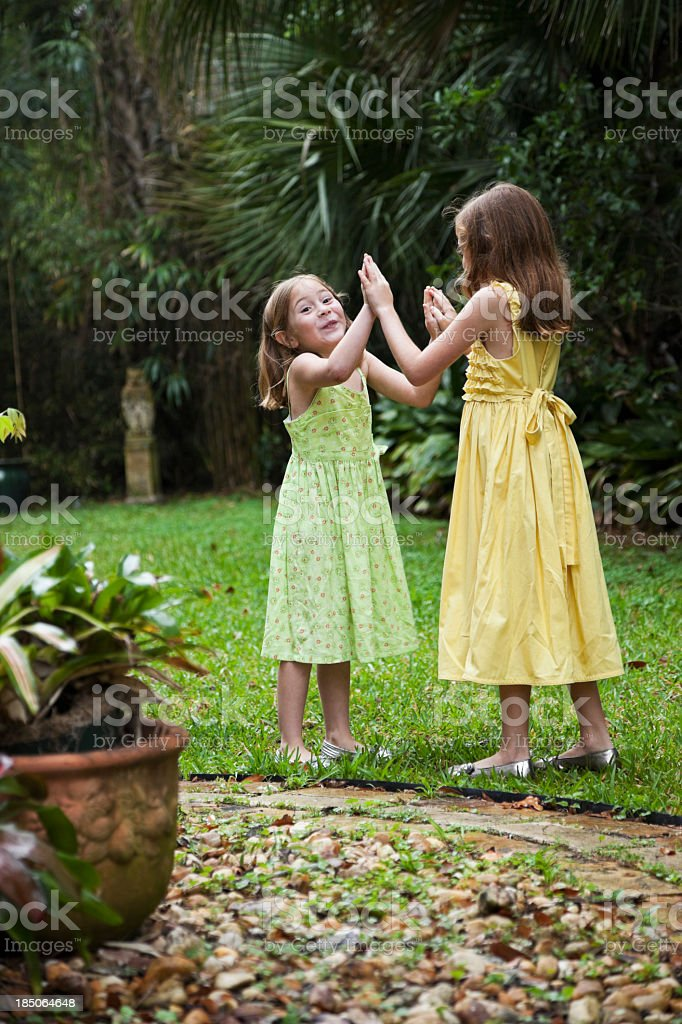 Little girls wearing sundresses playing in back yard royalty-free stock photo