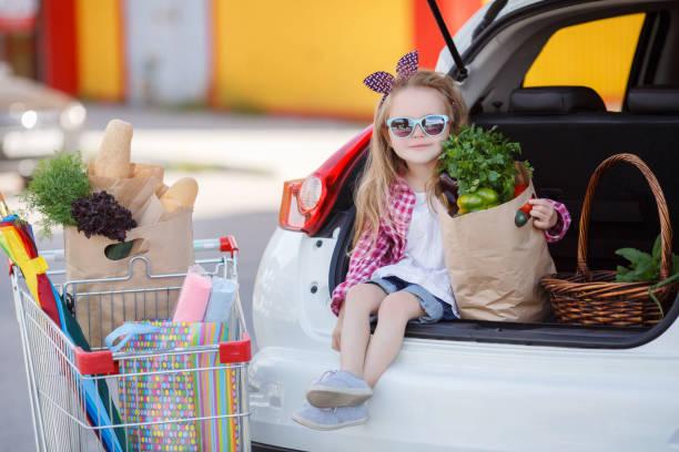 kleine mädchen-die käufer von produkten, in den offenen kofferraum eines autos sitzen - taschen von liebeskind stock-fotos und bilder