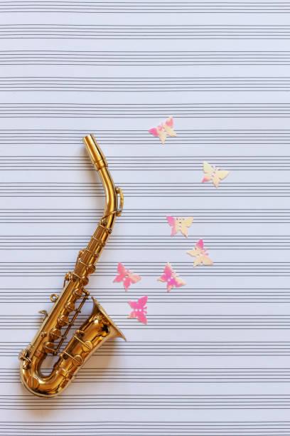 Pouco saxofone dourado e figurines da borboleta do glitter. Vista superior, close-up no fundo do papel de nota - foto de acervo