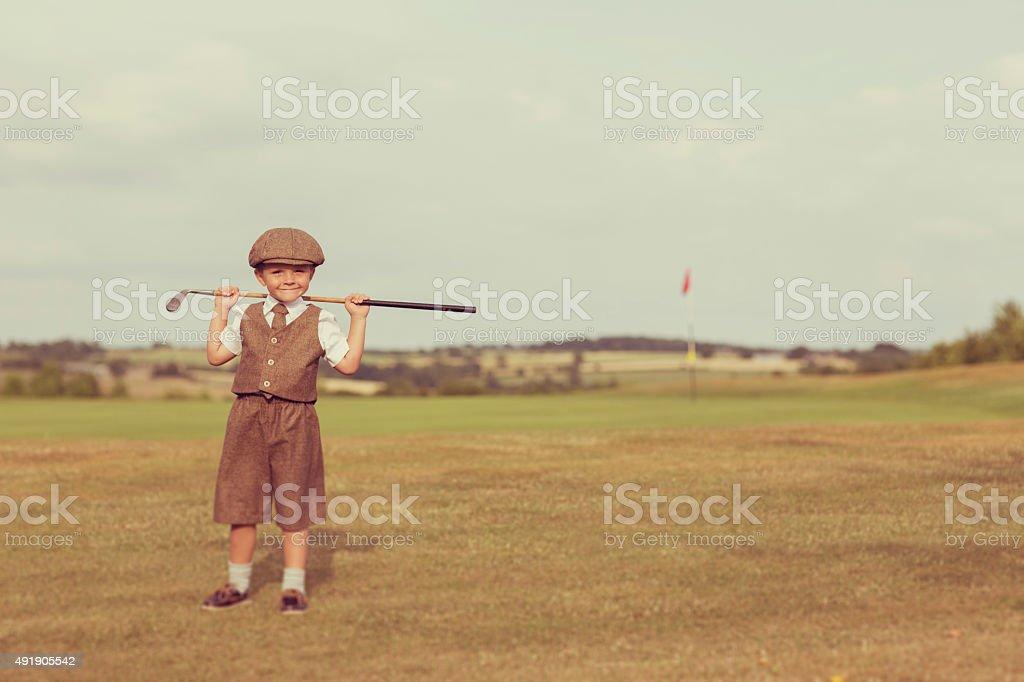 Little Golfing Boy in Vintage Attire stock photo