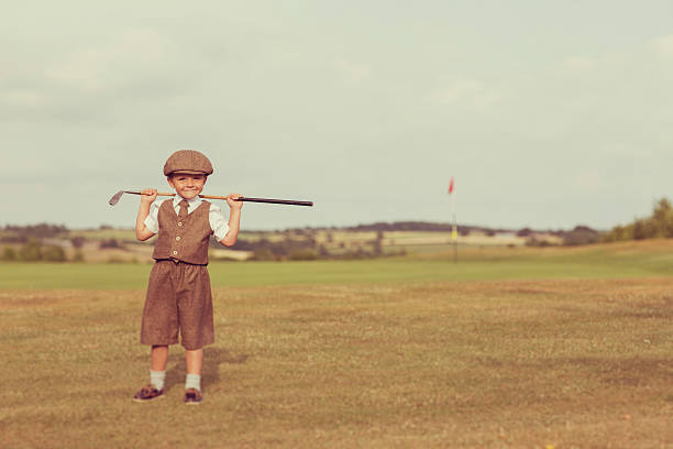 Little Golfing Boy in Vintage Attire A little boy dressed in vintage golfing attire stands with his club on a golf course in England. He is standing by the putting green and is smiling because he loves golf. child prodigy stock pictures, royalty-free photos & images