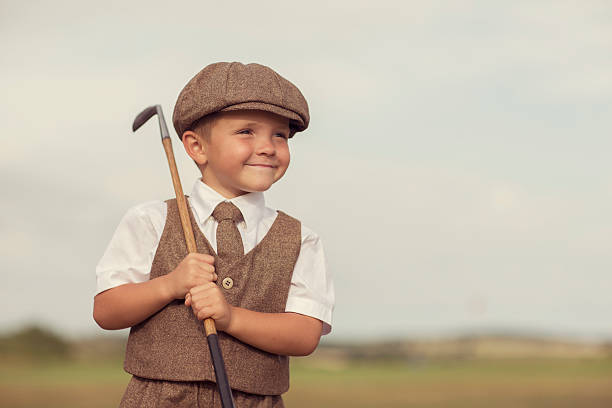 Little Golfing Boy in Vintage Attire A little boy dressed in vintage golfing attire stands with his club on a golf course in England. He is wearing a vest and tie with a vintage hat. He is smiling because he loves golf. child prodigy stock pictures, royalty-free photos & images
