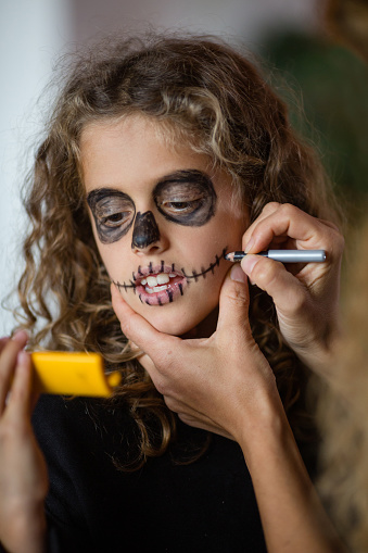istock Little goth girl putting make-up on face, looking in small yellow mirror 1058566440