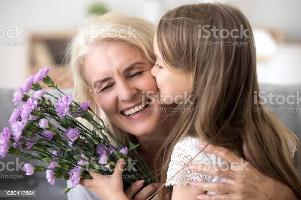 Little granddaughter kissing giving flowers bouquet congratulating picture id1080412564?b=1&k=6&m=1080412564&s=612x612&h=hdjo38eidzpphhh39sfc2astyryopkrxsr2r jd3wtu=
