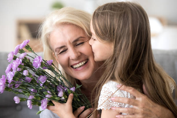 Little granddaughter kissing giving flowers bouquet congratulating smiling old grandmother Little preschool granddaughter kissing happy older grandma on cheek giving violet flowers bouquet congratulating smiling senior grandmother with birthday, celebrating mothers day or 8 march concept granddaughter stock pictures, royalty-free photos & images