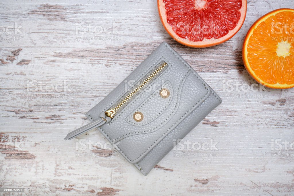 Little gray female purse, and citrus on a sweater. Fashionable concept. stock photo