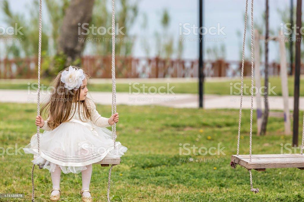 little gırls child swinging in field stock photo