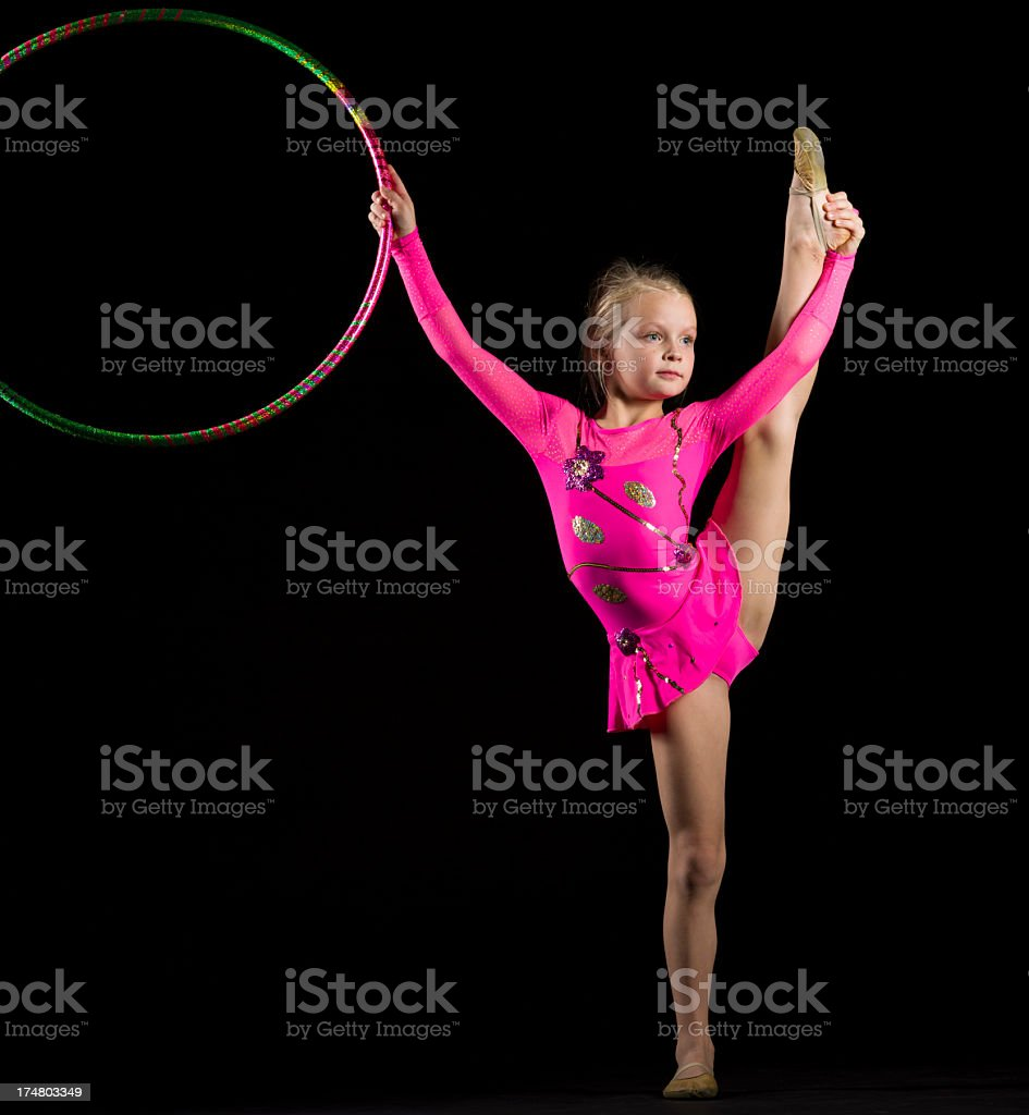 Little Gymnast girl with hula hoop on black background royalty-free stock photo