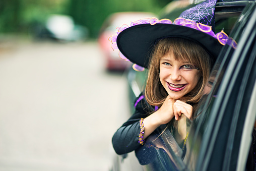 Portrait of a little girl during halloween dressed up as a witch. The girl is aged 9 and is smiling from the car window. Street visible in the background and a lot of nice copy space.
