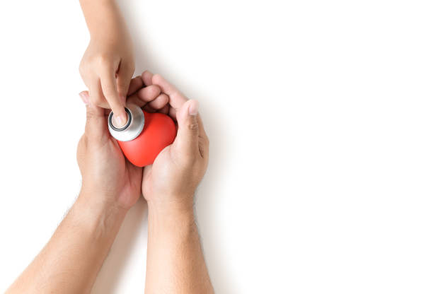 Little hand holding stethoscope to checking red heart stock photo