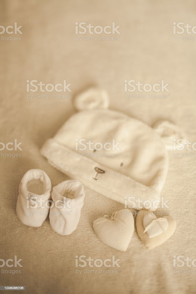 Little hand made baby clothes. Photo of ultrasound. newborn clothes on beige woolen background. Happiness stock photo
