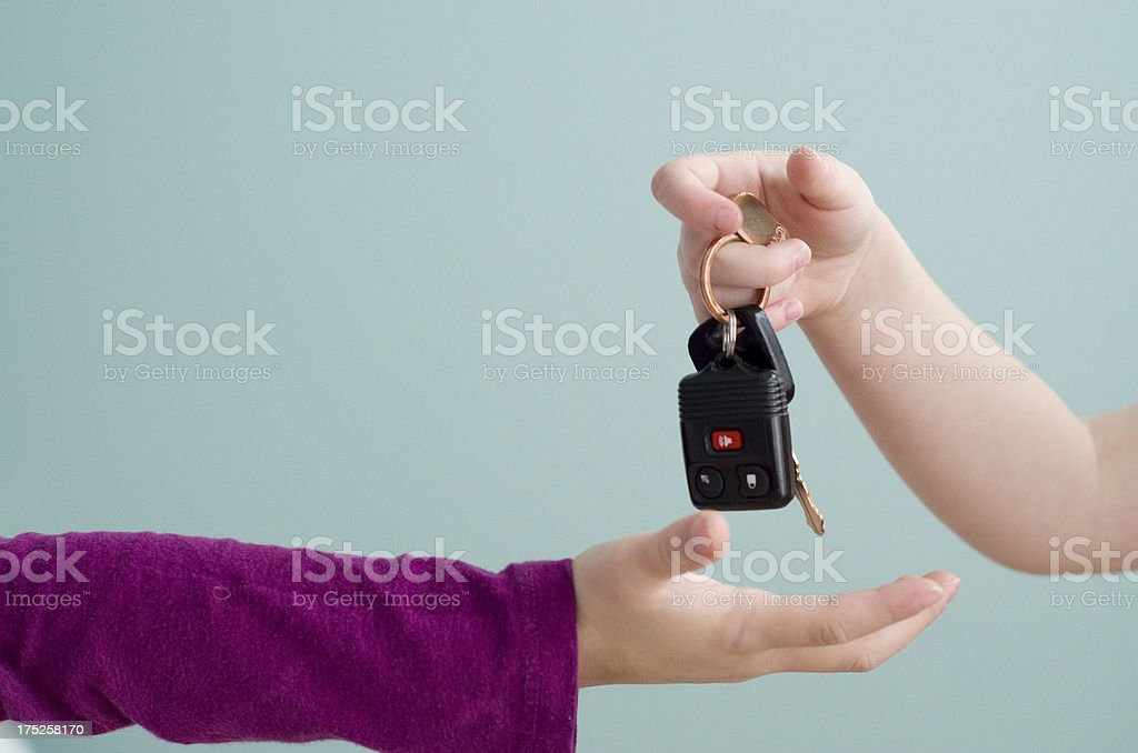 Little hands giving and receiving car keys stock photo