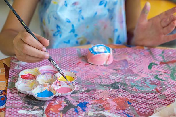 little hands of kid painting on the plaster soft focus. - handbemalte teller stock-fotos und bilder
